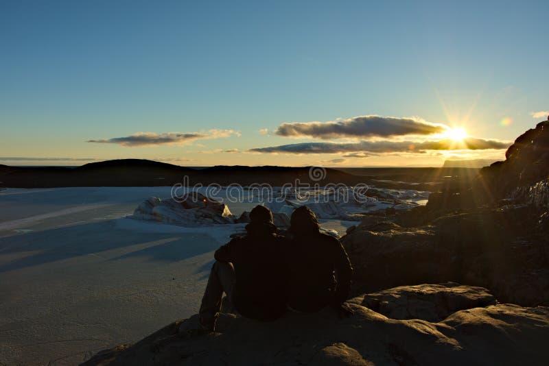 Le couple apprécie le coucher du soleil au-dessus du glacier images libres de droits