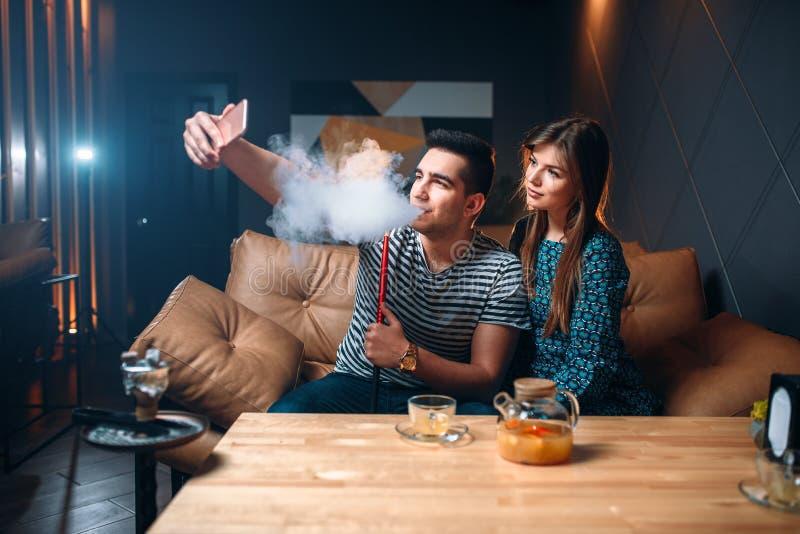 Le couple d'amour fume le narguilé à la barre images stock