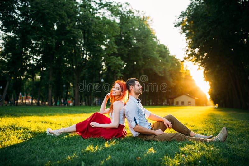 Le couple d'amour se repose sur l'herbe en parc, date romantique images stock