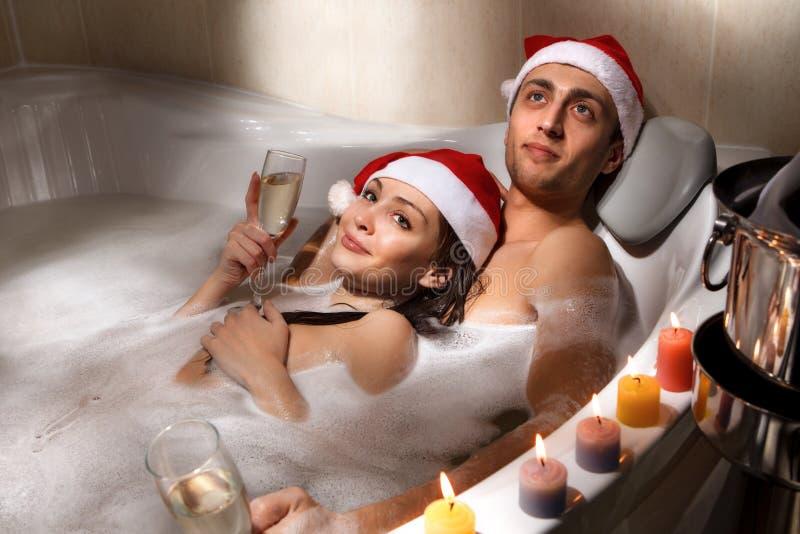 Le couple dans des chapeaux de Santa apprécie un bain photos libres de droits