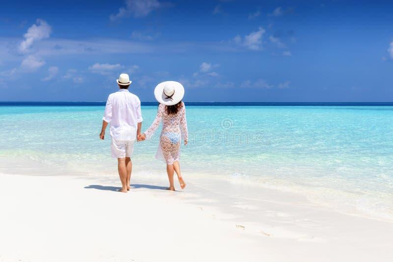 Le couple dans des v?tements blancs d'?t? marche le long d'une plage tropicale photographie stock libre de droits