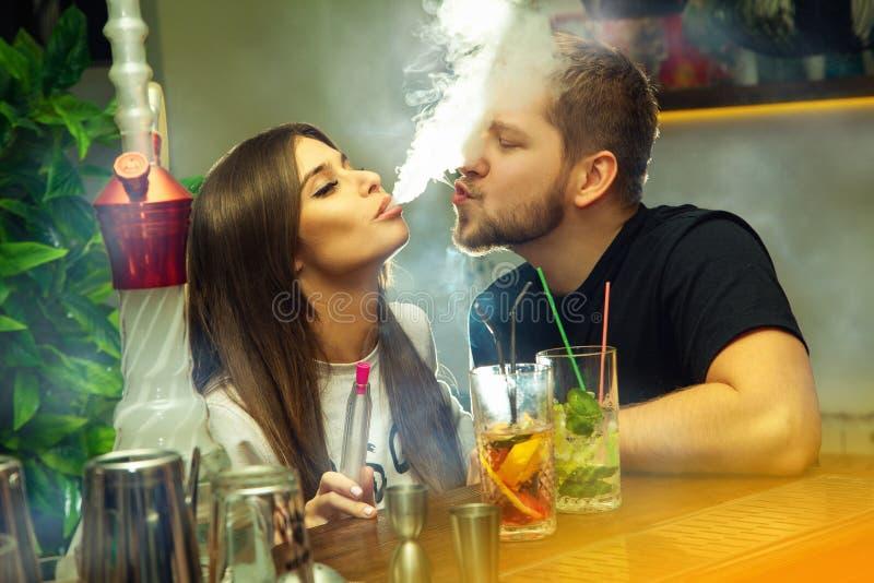 Le couple dans l'amour fume le narguilé et boit des cocktails image stock
