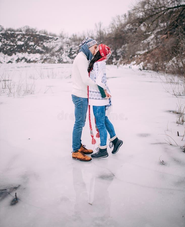 Le couple dans les chapeaux et des écharpes est s'élevant et embrassant au lac congelé pendant la promenade d'hiver photo stock