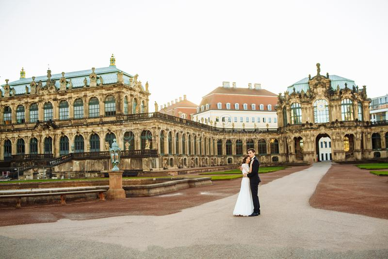 Le couple de luxe heureux de mariage est se tenant et embrassant dans les rues de la vieille ville photos stock