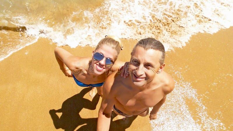 Le couple de sourire fait un selfie sur la plage image stock