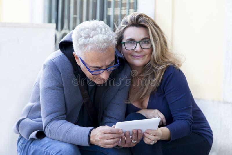 Le couple des personnes mûres consulte le smartphone image stock