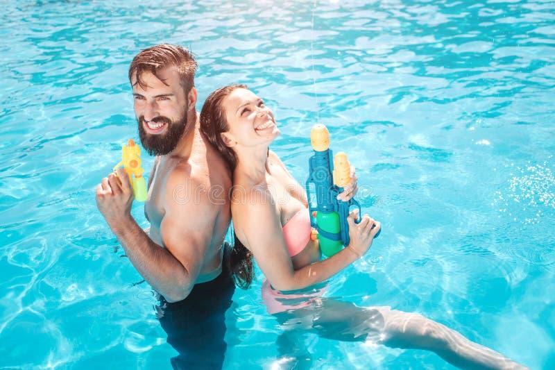 Le couple drôle se tient dans la piscine Ils posent et sourient La fille recherche Ils tiennent des revolvers d'eau en mains Ils  image stock