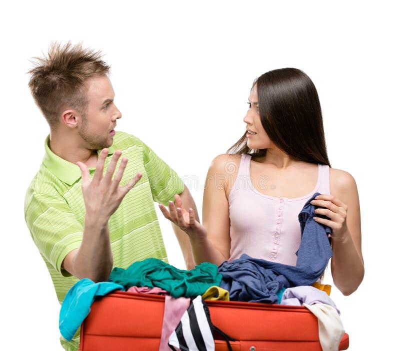 Le couple emballe la valise avec l'habillement pour le départ photo stock