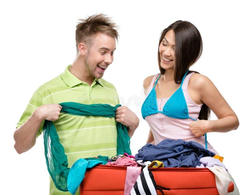 Le couple emballe la valise avec l'habillement pour le déplacement images libres de droits