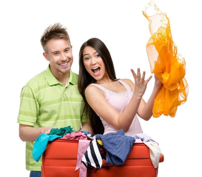 Le couple emballe la valise avec l'habillement pour le voyage photo stock