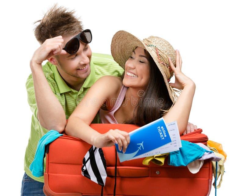 Le couple emballe la valise avec l'habillement pour le voyage photo libre de droits