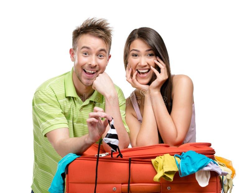 Le couple emballe la valise avec l'habillement pour le voyage photos libres de droits