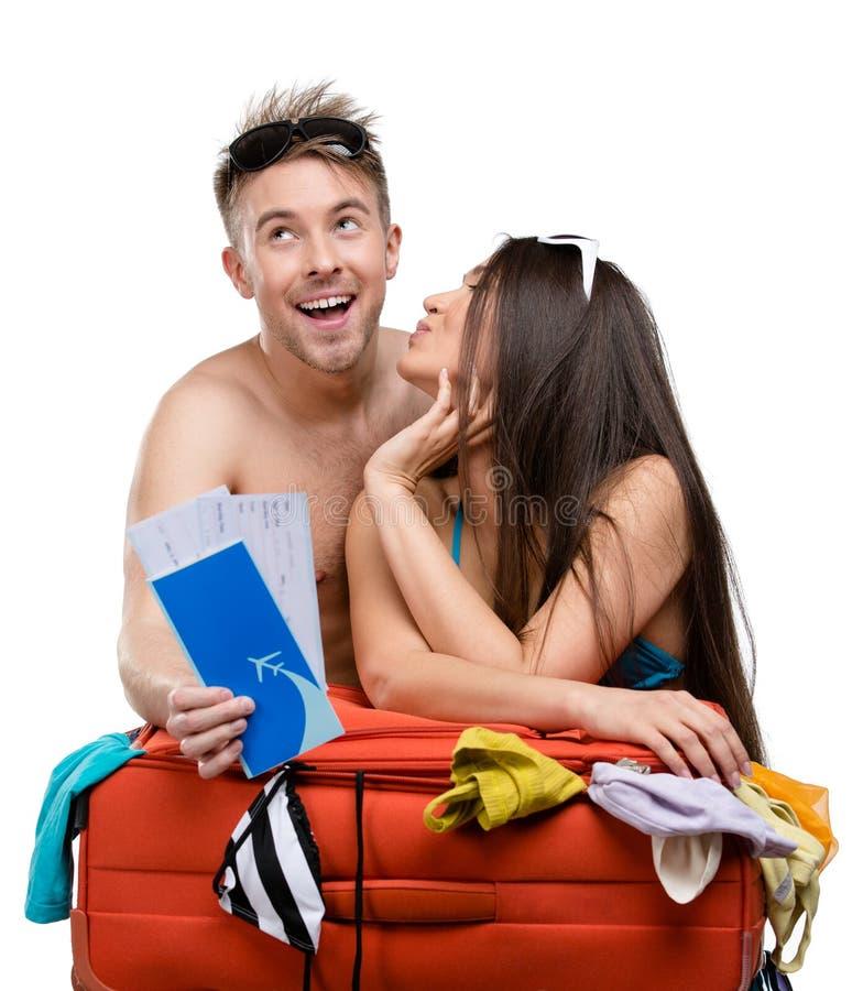 Le couple emballe la valise et essaye l'habillement pour le déplacement image libre de droits