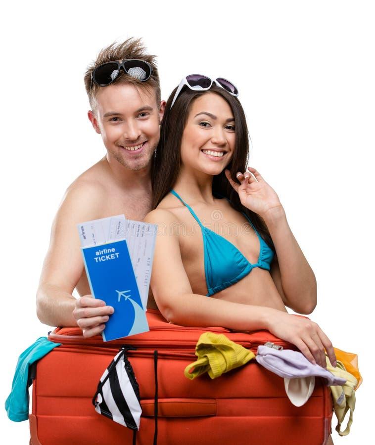 Le couple emballe la valise et essaye l'habillement pour le voyage image libre de droits