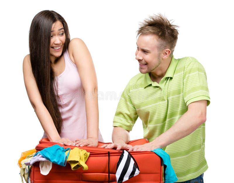 Le couple emballe vers le haut de la valise avec l'habillement pour le voyage image libre de droits