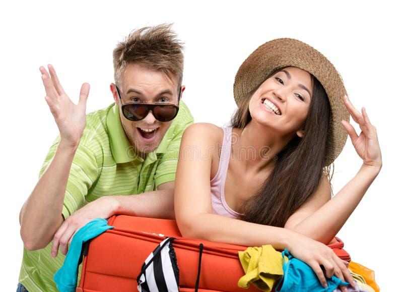 Le couple emballe vers le haut de la valise avec l'habillement pour le voyage photographie stock libre de droits