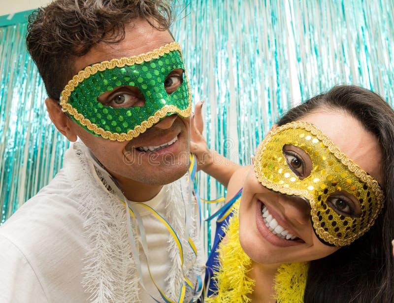 Le couple emploie des masques de Carnaval au Brésil, ils regarde l'appareil-photo image stock