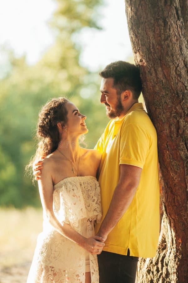 Le couple enamouré par jeunes sourit, étreint et tient des mains dans la forêt photos stock