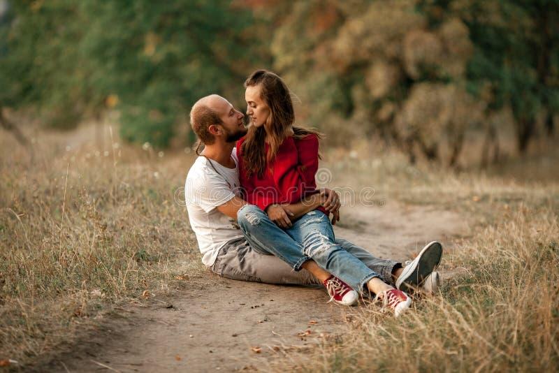 Le couple enamouré se repose et des étreintes sur le chemin forestier photos libres de droits