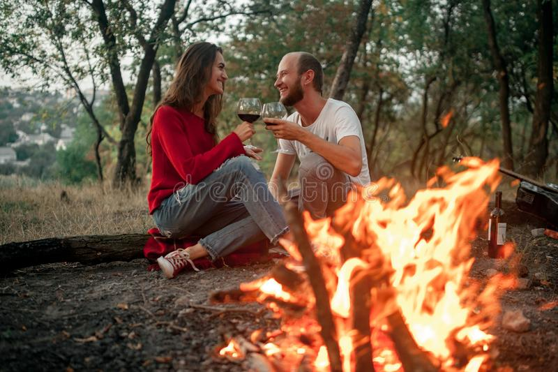 Le couple enamouré se repose et sourit sur le pique-nique dans la forêt sur le feu f images libres de droits