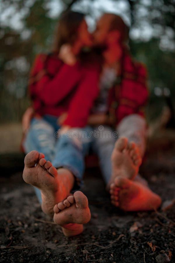 Le couple enamouré se repose sur le pique-nique dans la forêt avec les pieds nus et le baiser photographie stock libre de droits