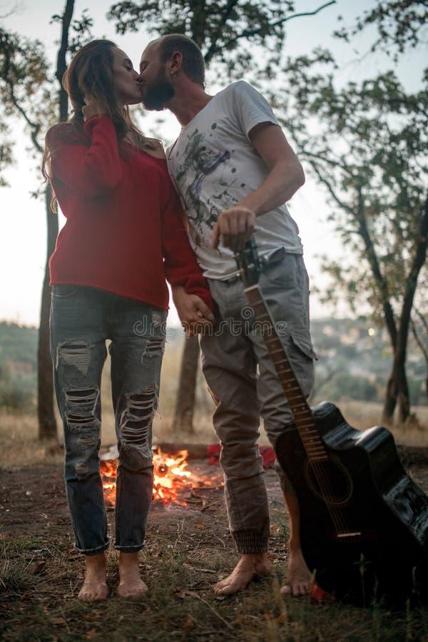 Le couple enamouré se tient avec la guitare et les baisers sur le pique-nique dans les avants photographie stock