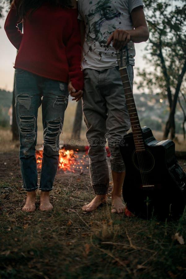 Le couple enamouré se tient avec la guitare sur le pique-nique dans la forêt photos libres de droits