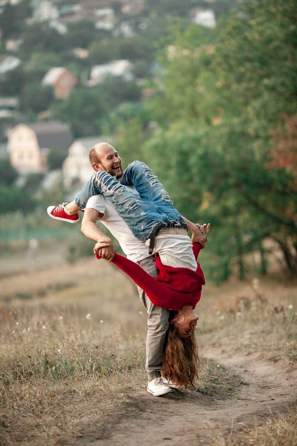 Le couple enamouré se tient, rit gaiement et se distrait sur la forêt photos libres de droits