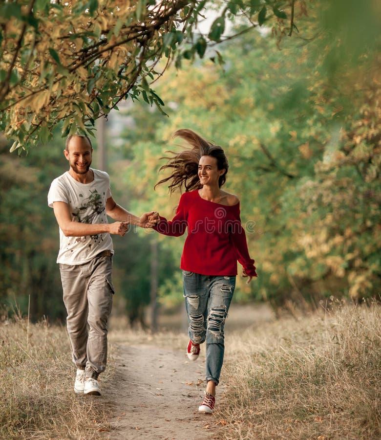 Le couple enamouré tient des mains et des courses sur le chemin forestier photographie stock
