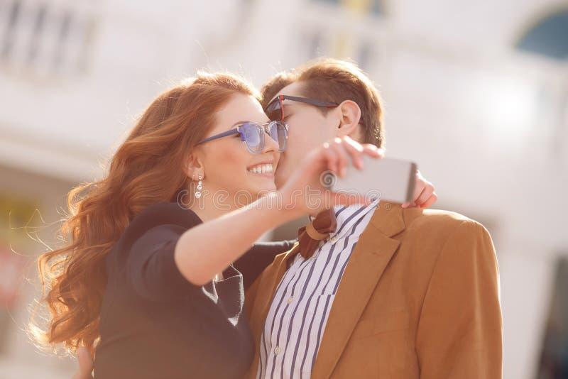 Le couple est photographié avec le smartphone dans la ville photographie stock