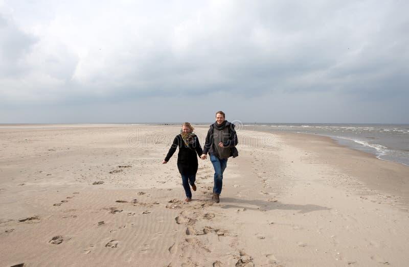 Le couple fonctionne sur la plage image libre de droits