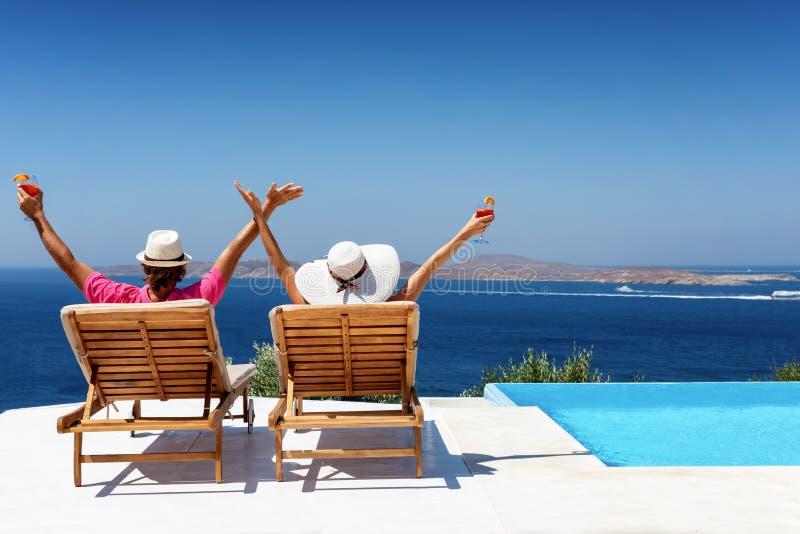 Le couple heureux apprécie leurs vacances de luxe par la piscine photographie stock