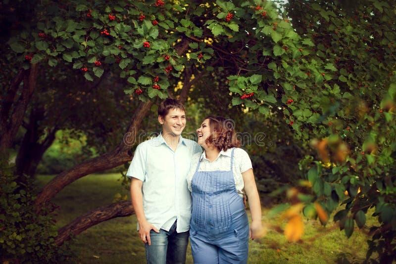 Le couple heureux attendant un bébé marche en été dans un beau pair photographie stock libre de droits