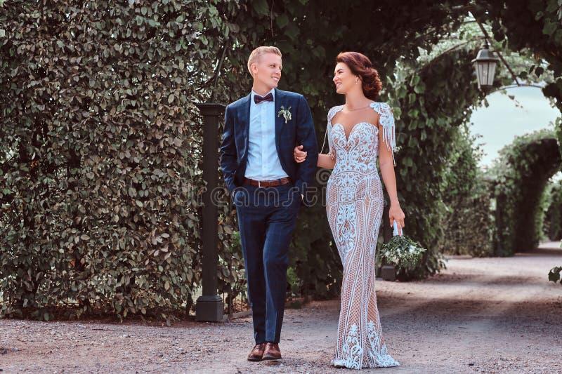 Le couple heureux de mariage marche par le jardin étonnant photographie stock libre de droits