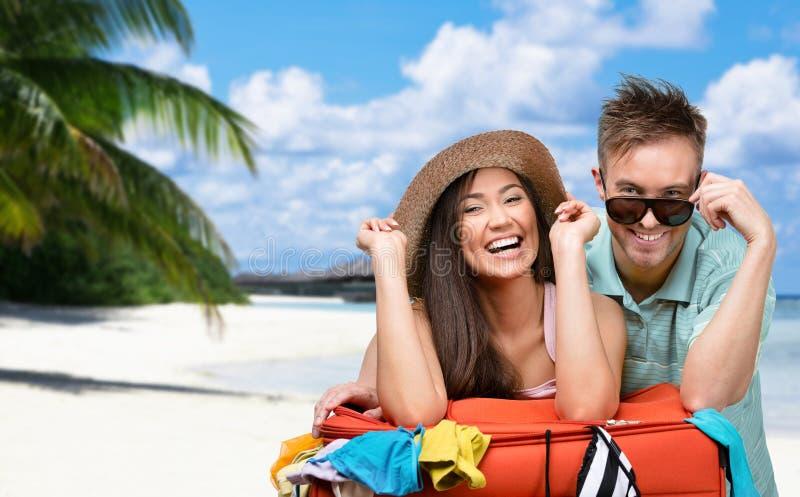 Le couple heureux emballe vers le haut de la valise avec l'habillement pour le déplacement images libres de droits