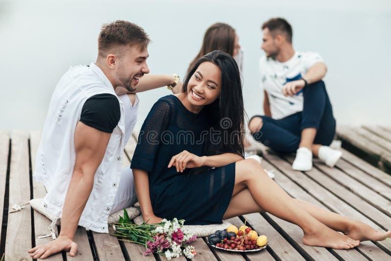 Le couple heureux a l'amusement se reposant par la rivière images libres de droits
