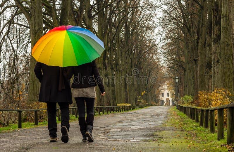 Le couple marche sous le parapluie d'arc-en-ciel image stock