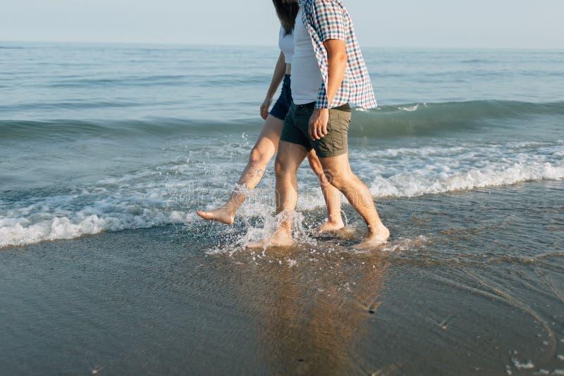 Le couple marche sur le bord de la mer image stock