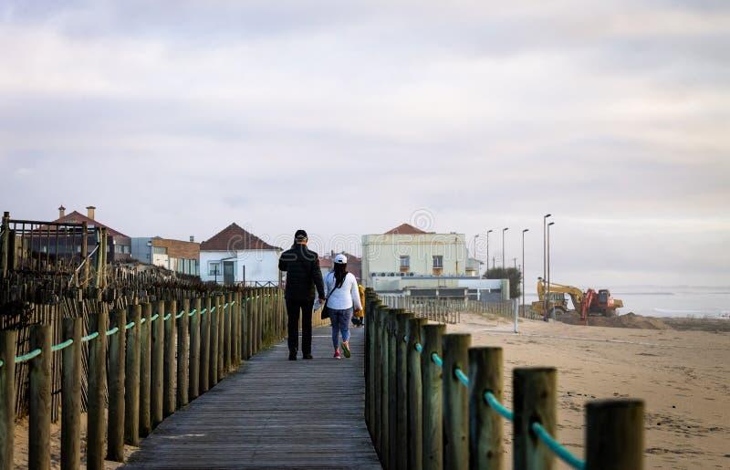 Le couple marche sur la promenade à la plage photos stock