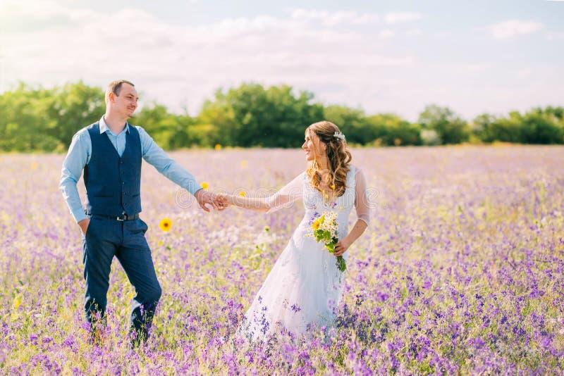 Le couple marié marchant dans le domaine des fleurs pourpres, la jeune mariée mène le marié derrière elle, la fille tient le type photos stock