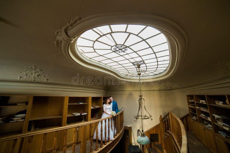 Le couple merveilleux de nouveaux mariés étreint dans le château baroque images stock
