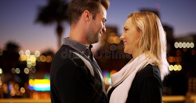 Le couple millénaire regardant dans l'un l'autre le ` s observe dehors la nuit images stock