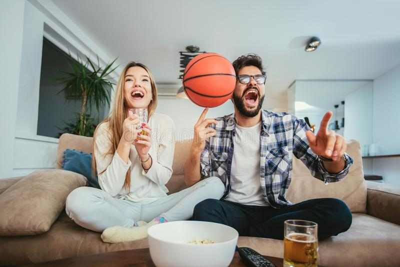 Le couple observe le match de basket sur le sofa images libres de droits