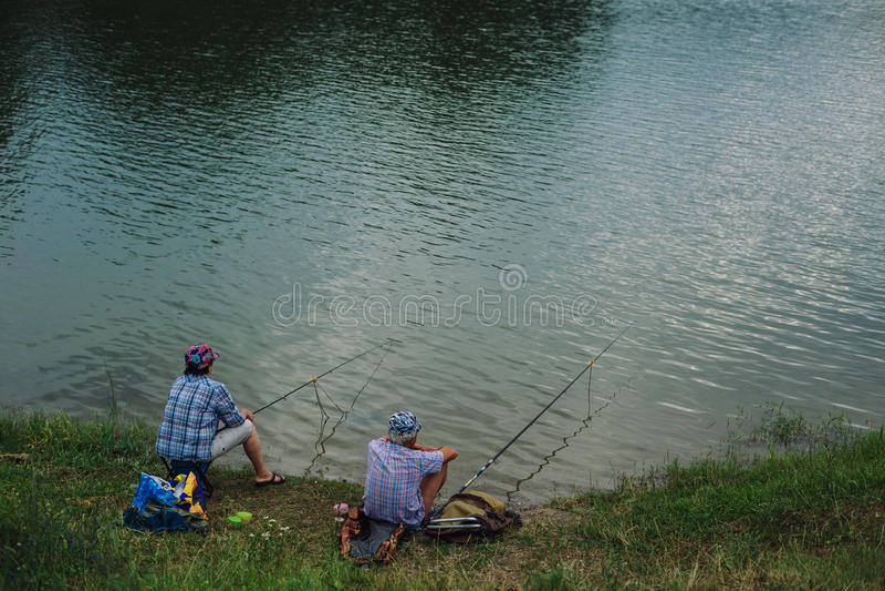 Le couple pêche des poissons avec une canne à pêche photographie stock