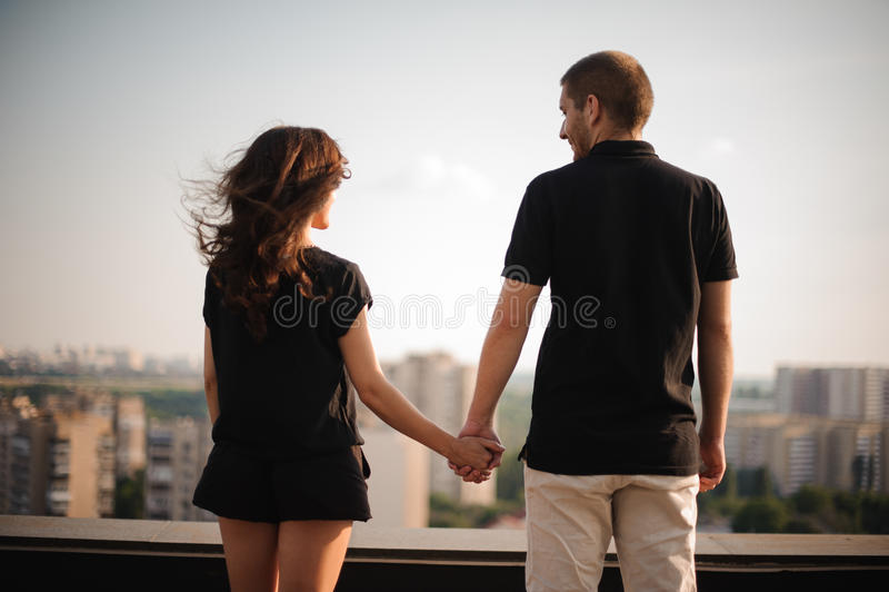 Le couple par derrière se tenir remet le regard sur la ville photographie stock libre de droits