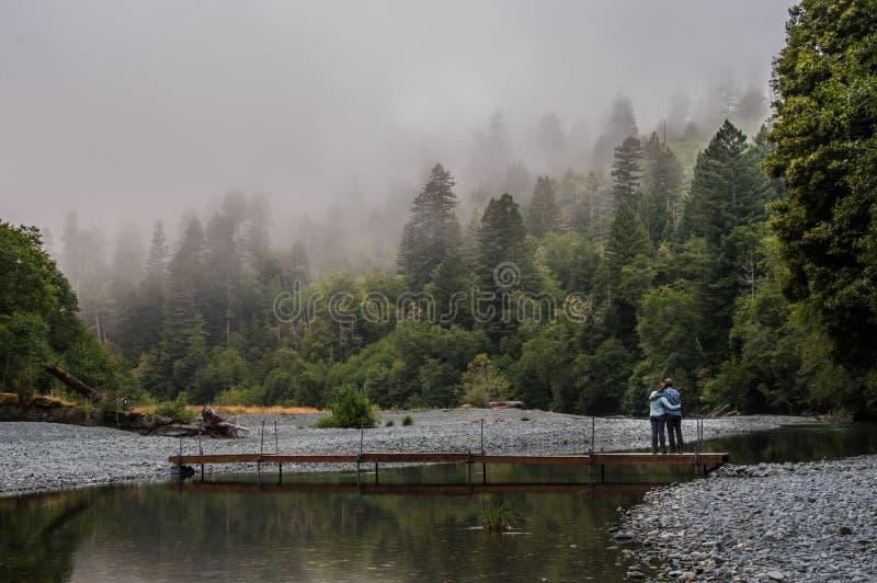 Le couple a plaisir à regarder une rivière calme de montagne photos libres de droits