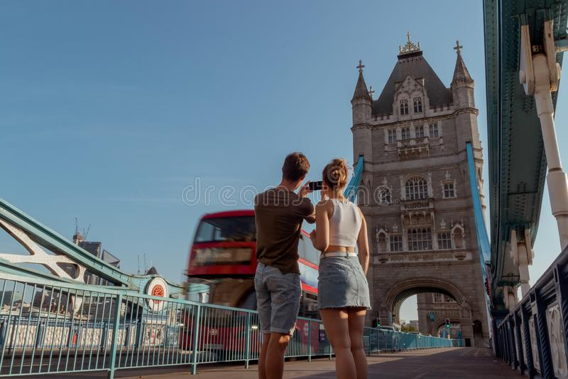 Le couple prend une photo d'un autobus à impériale rouge sur le pont de tour à Londres image stock