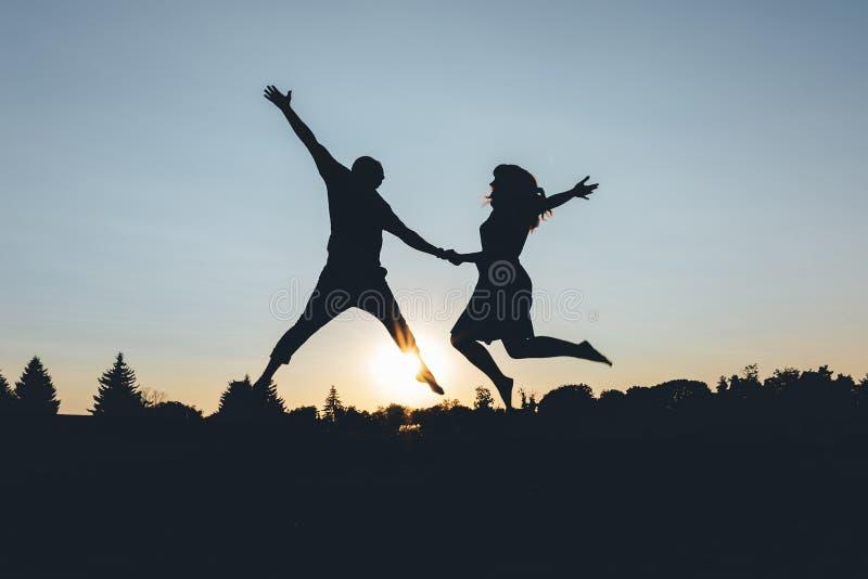 Le couple rebondit tenant des mains sur le coucher du soleil, cadre de silhouette photographie stock libre de droits