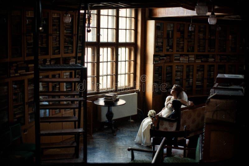 Le couple regarde la fenêtre dans la vieille bibliothèque images stock