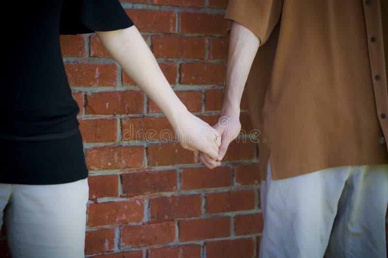 le couple remet des jeunes de fixation photo stock